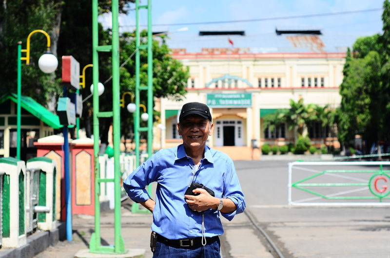 Portrait of senior man holding camera on road against built structure