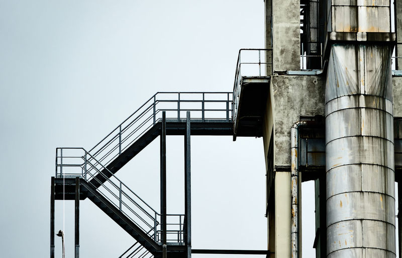iron staircase next to an aluminium pipe at the tower of an industrial plant