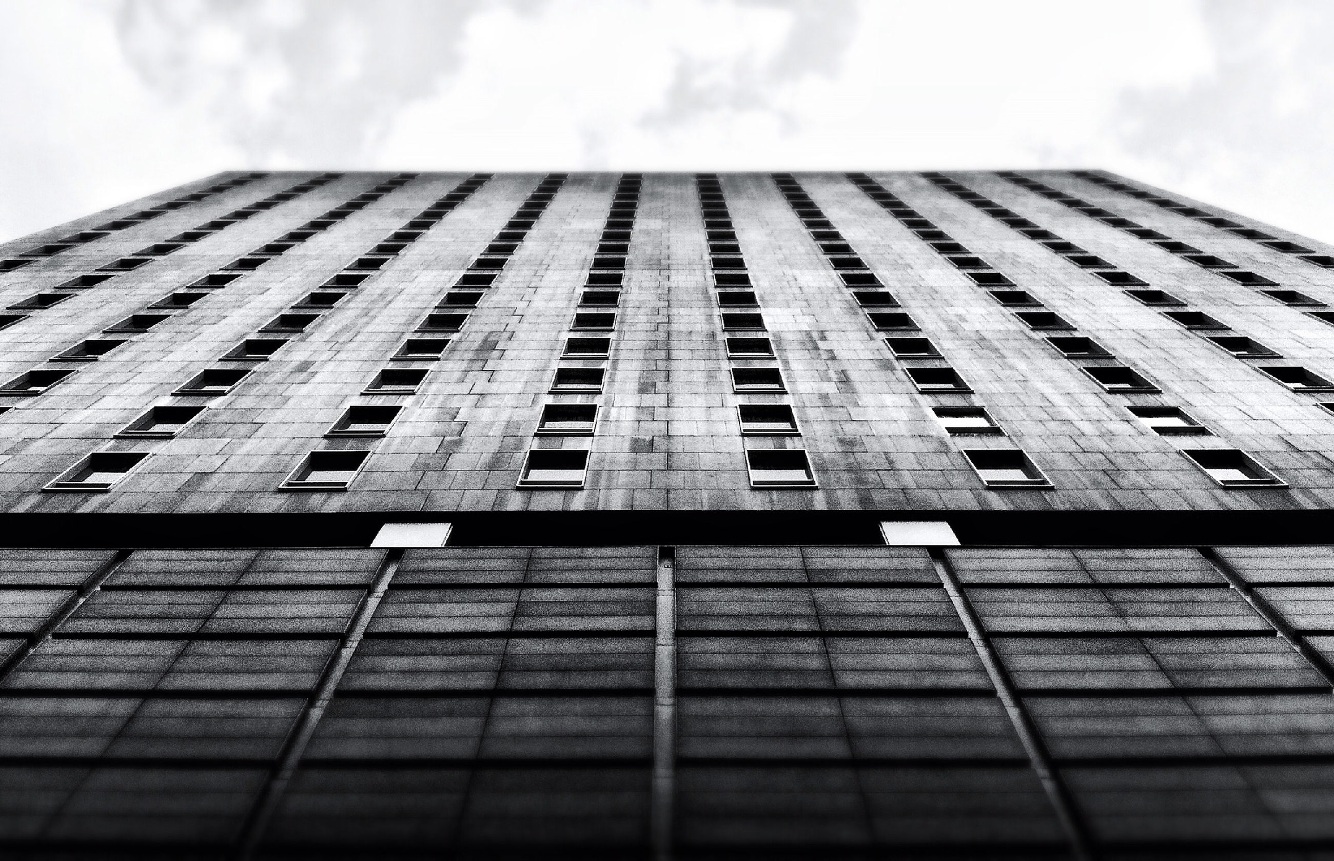 architecture, built structure, building exterior, low angle view, sky, tall - high, modern, office building, tower, building, skyscraper, cloud - sky, city, day, pattern, glass - material, tall, window, outdoors, no people