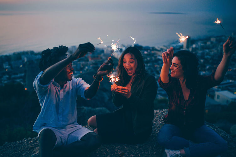 High angle view of happy friends burning sparklers while sitting on mountain at night