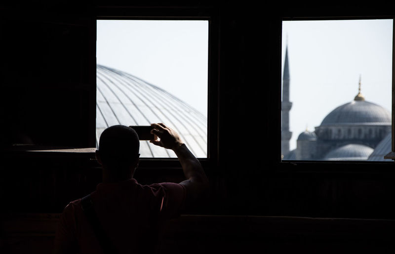 Rear view of man photographing through window