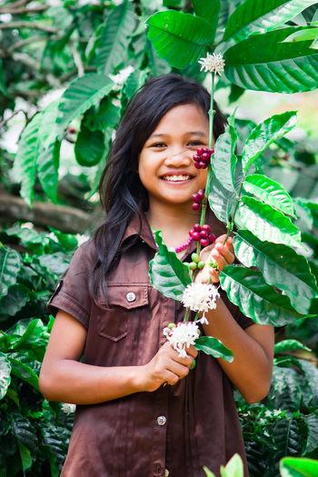 Portrait of smiling girl holding plant