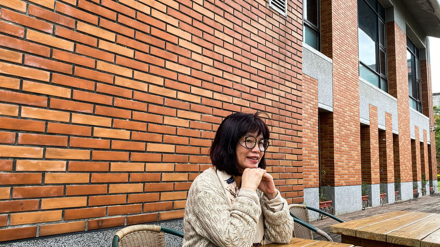 Portrait of woman sitting against brick wall