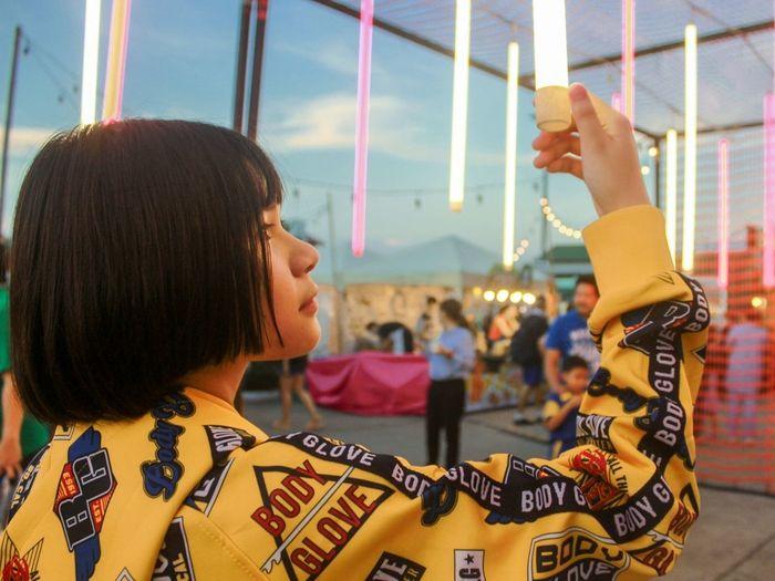 Portrait of girl holding carousel at amusement park