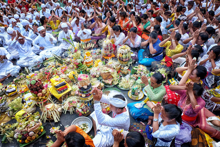 High angle view of people with hands clasped praying outdoors