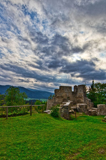 Old ruin on field against cloudy sky