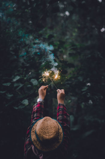 Rear view of woman holding sparklers in forest