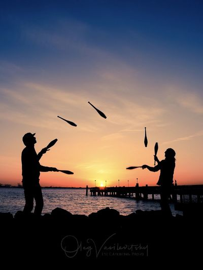 Silhouette Men Juggling Pins At Beach Against Sky During Sunset