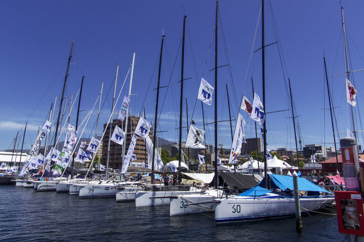 Sailboats moored at harbor against clear blue sky