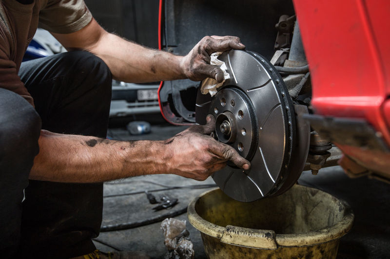 man changing brakes car at home. Brakes Close-up Craft Finger Hand Holding Human Body Part Human Hand Indoors  Industry Machinery Mechanic Men Metal Midsection Occupation One Person Real People Skill  Wheel Working Workshop