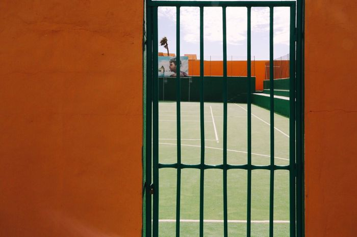 Window Non-urban Scene Barrels Barrier Sport Landscape Green Color Orange Color Wall - Building Feature Door Closed Playground Ground Tenniscourt Day Architecture Built Structure Real People Close-up Sky Railing