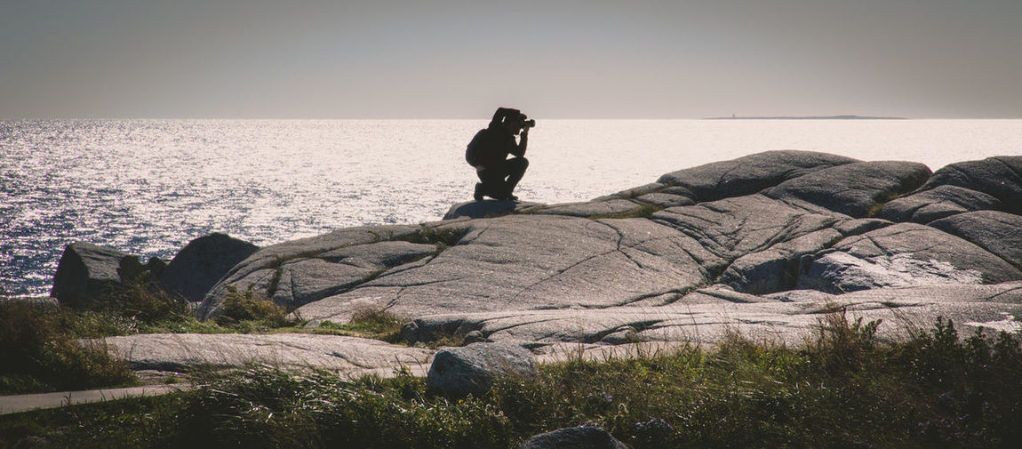Man Photographing On Rock Against Sea