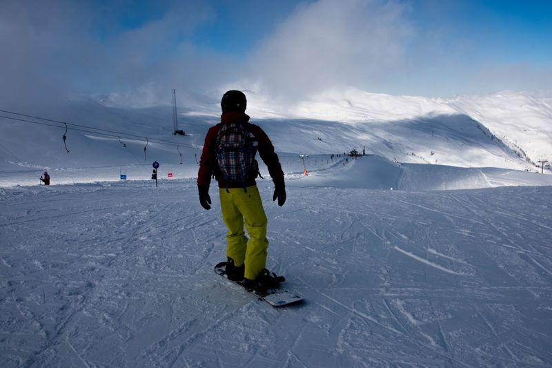Rear view of man skiing on snow covered landscape