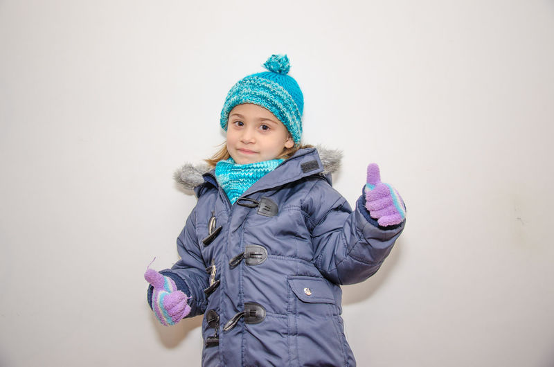 Portrait of cute girl wearing warm clothing showing thumbs up sign against wall