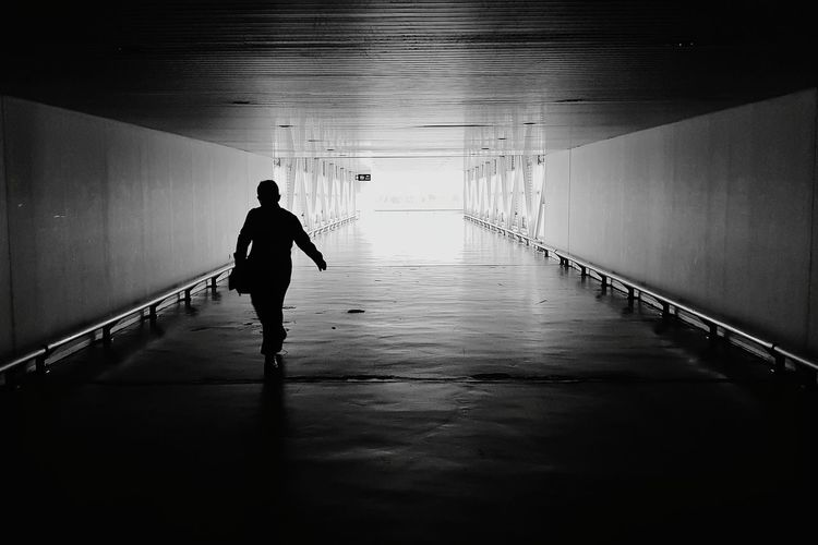 Full Length Of Silhouette Man Walking In Tunnel