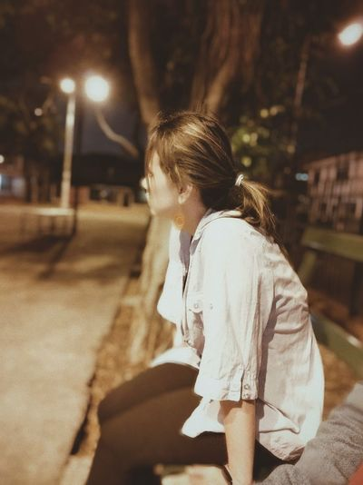 Side view of woman sitting on bench in park at night