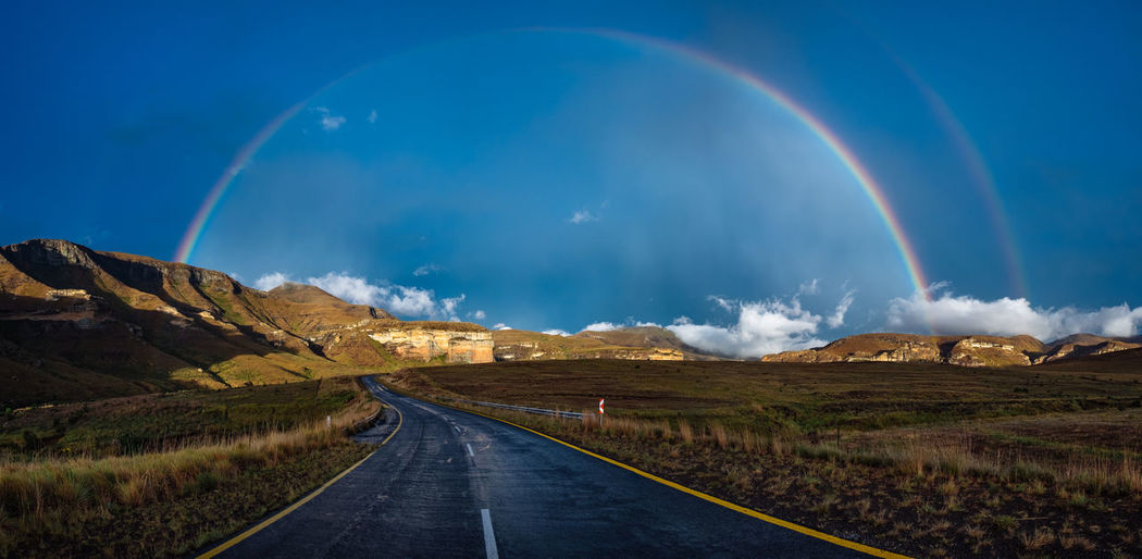 Empty road against rainbow in blue sky at golden gate highlands national park