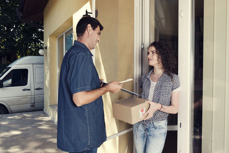 Delivery Man Giving Pen And Clipboard To Woman Against House