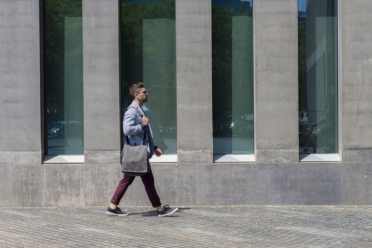 Full length of woman walking by building in city