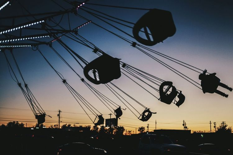 Illuminated silhouette chain swing ride against sky during sunset