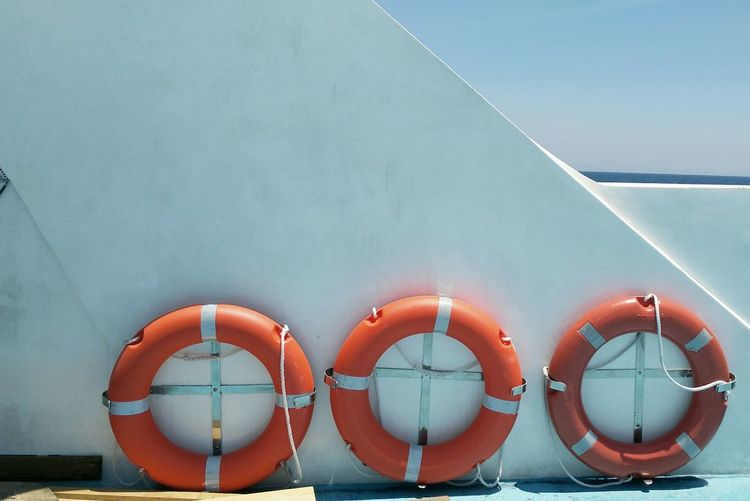 Life belts by wall on boat against clear sky