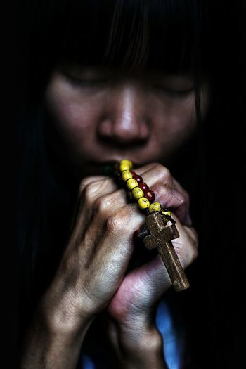 Woman holding rosary against black background