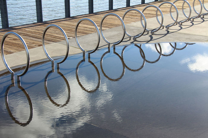 Circular bike racks reflect with small white clouds in a giant puddle along the boardwalk. Background Bike Racks Biking Boardwalk British Columbia Canada Circular Close-up Clouds Day Dreamy Excercising EyeEmNewHere Metal Nature No People Outdoors Park Repetition Sky Walkway Water Water Reflections Water_collection Wood First Eyeem Photo