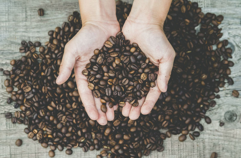 Cafe time Abundance Arm Body Part Brown Cafe Cafe Time Caffeine Coffee Coffee - Drink Finger Food Food And Drink Freshness Hand Hands Cupped High Angle View Holding Human Body Part Human Hand Indoors  Large Group Of Objects One Person Real People Roasted Coffee Bean