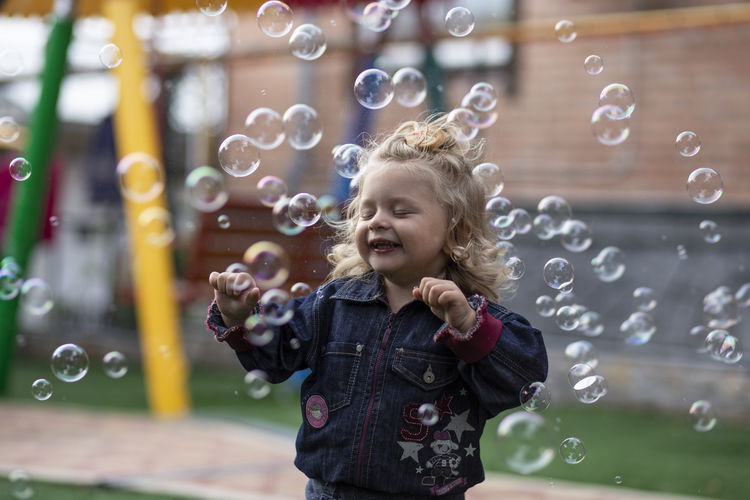 Cute smiling girl standing amidst bubbles