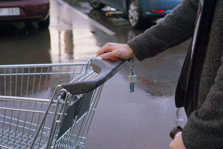 Midsection of man holding shopping cart in parking lot