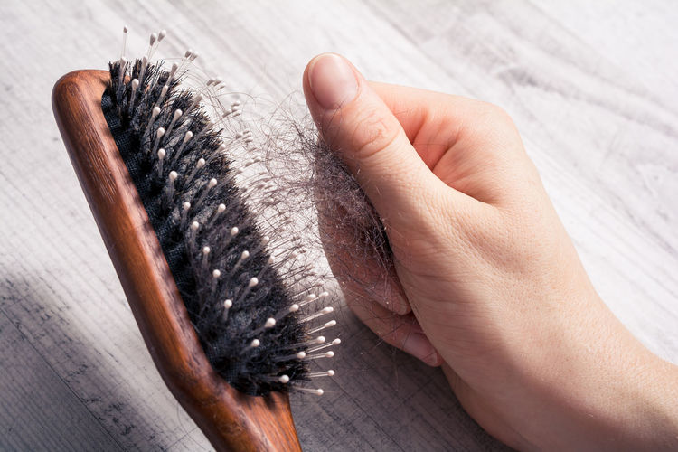 Close-up of hand removing hair from brush on table