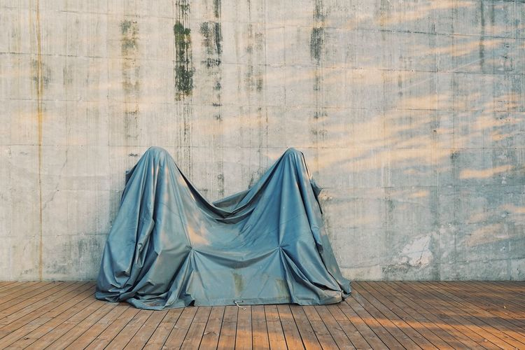 Covered Object With Fabric Against Wall On Floorboard