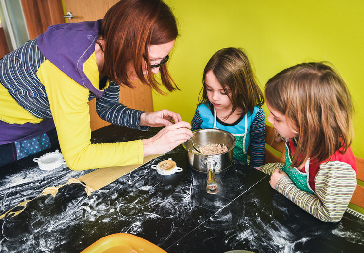 High angle view of mother with daughters preparing food in kitchen