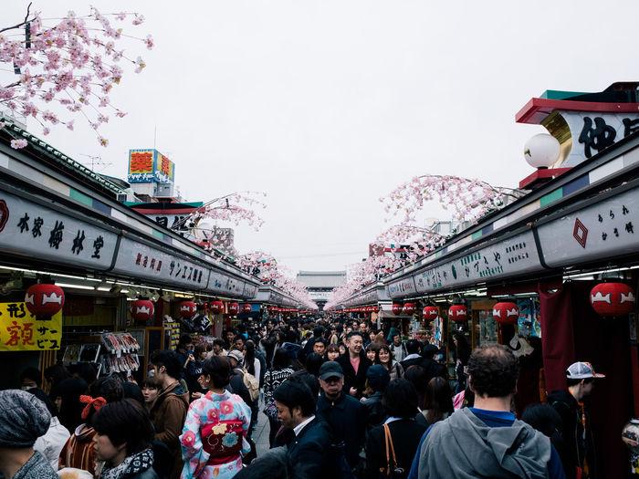 People on street market against sky in city