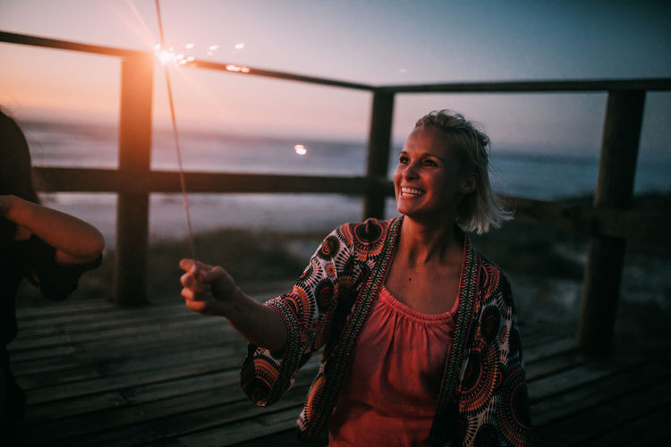 Happy woman standing by sea against sky during sunset