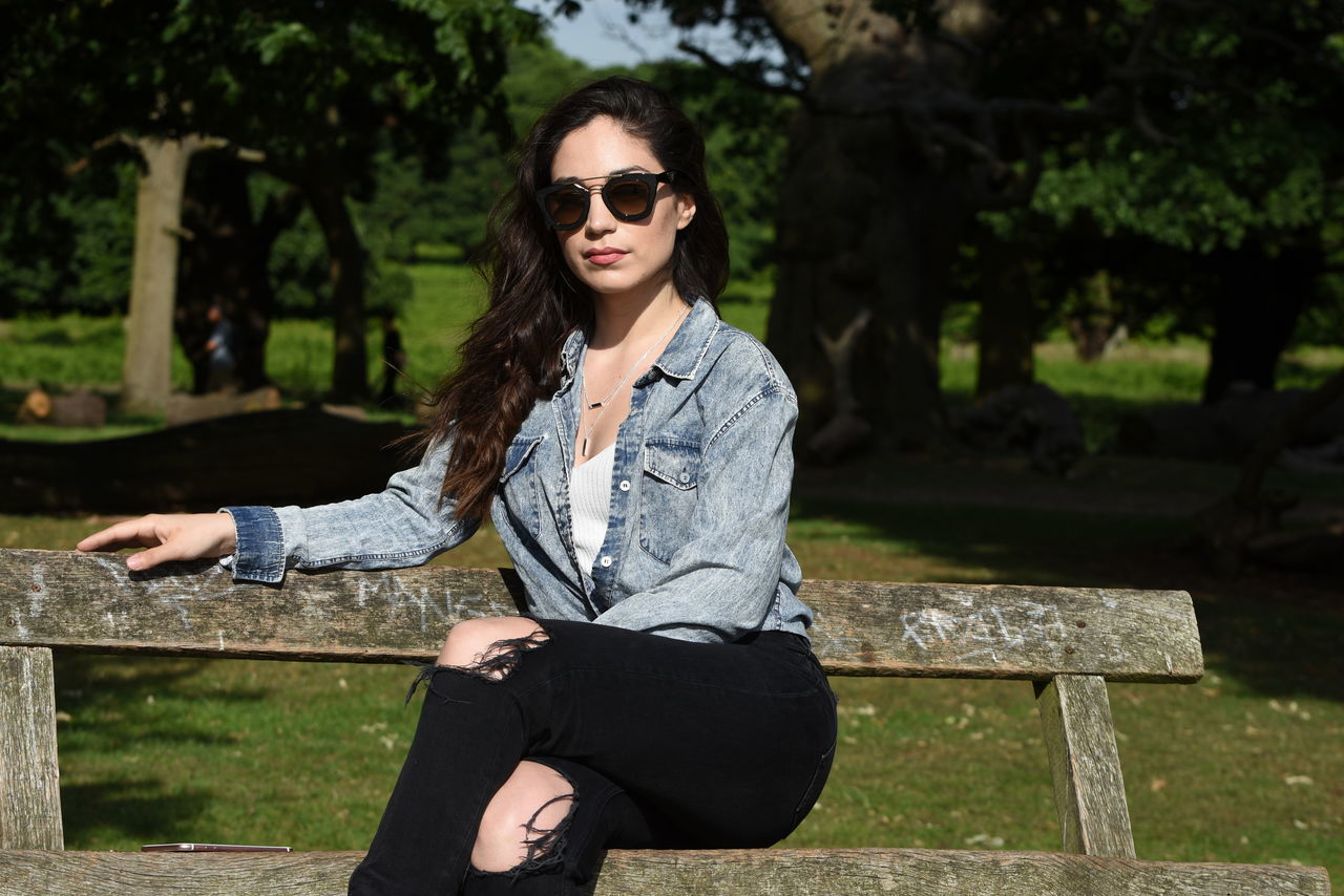 Portrait Of Beautiful Woman Sitting On Wooden Bench At Park