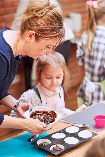 Mother with daughter preparing cupcakes at home