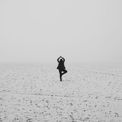 Rear view of woman doing yoga in snowy field