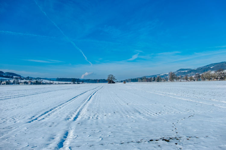 Snow Covered Field Against Blue Sky