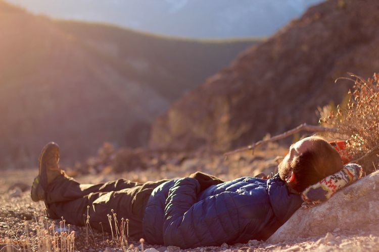 Low section of man lying on mountain