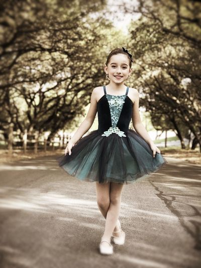 Portrait of smiling girl in dress standing on footpath at park