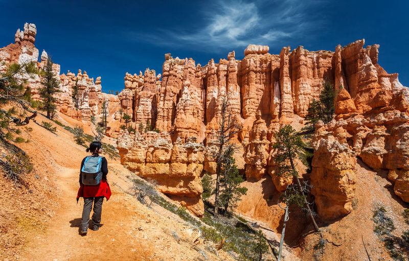 Rear view of female hiker hiking queens garden trail at bryce canyon national park