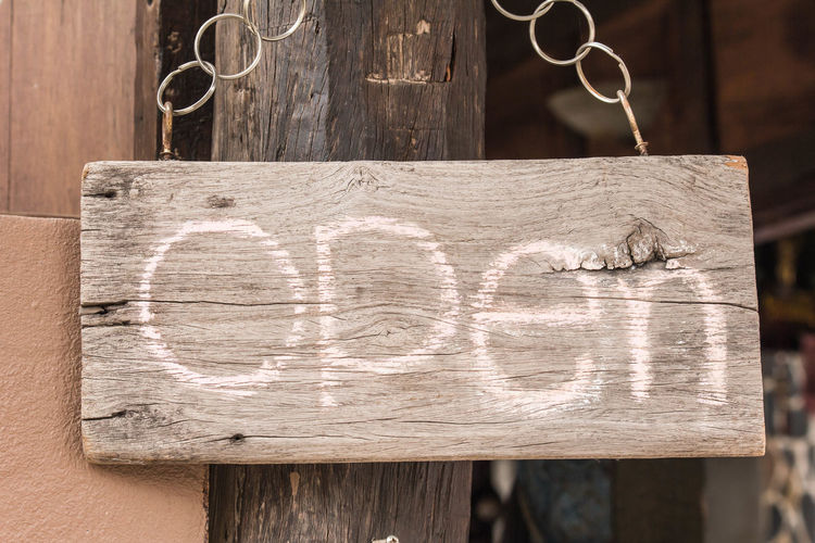 Close-up of open sign hanging on wood