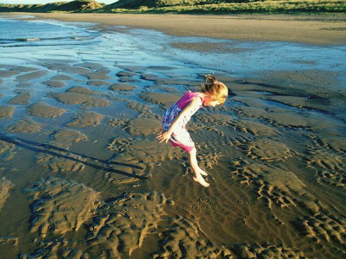 High angle view of girl jumping at beach