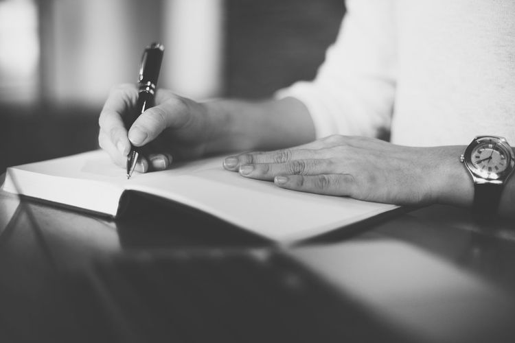 Midsection of woman writing in diary at table