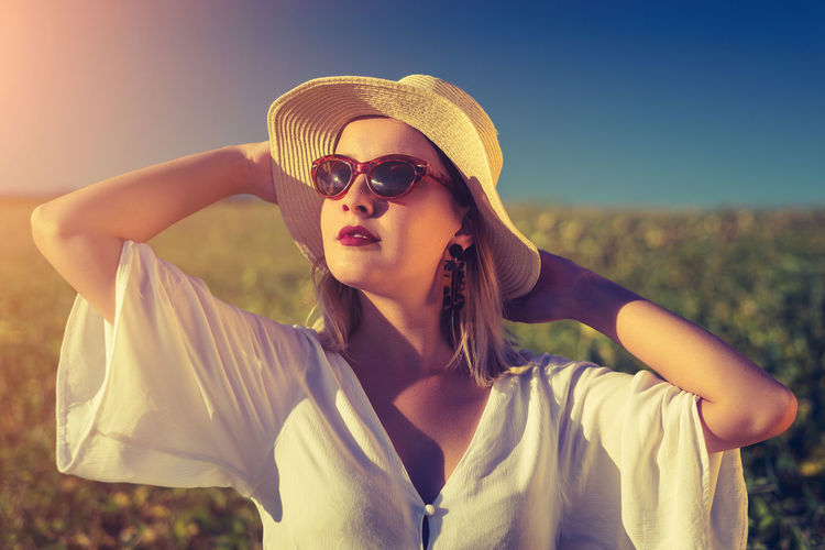 Beautiful young woman wearing sunglasses standing on land against sky