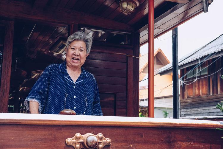 Portrait of a smiling senior woman standing tran