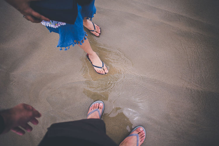 Low Section Of Man And Woman Standing On Beach