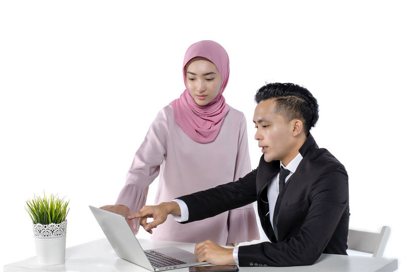 portrait of young couple entrepreneurs discussing ideas with a laptop in front of them Business Laptop Technology Two People Computer Business Person Wireless Technology Using Laptop Men Indoors  Table Connection Communication Young Men Waist Up Adult White Background Males  Young Adult Occupation Teamwork