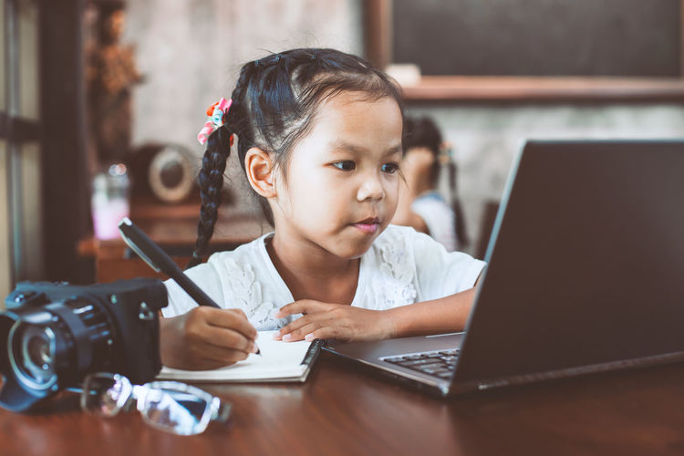 Schoolgirl Writing While Using Laptop In Classroom